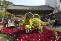 People wearing face masks to help curb the spread of the coronavirus pass by dinosaurs made of chrysanthemum flowers during the Chrysanthemum festival at the Chogyesa temple in Seoul, South Korea, Monday, Oct. 19, 2020. South Korea on Monday began testing tens of thousands of employees of hospitals and nursing homes to prevent COVID-19 outbreaks at live-in facilities. (AP Photo/Ahn Young-joon)