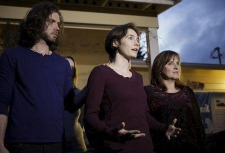 Amanda Knox (C) talks to the press, flanked by her her fiance Colin Sutherland and mother Edda Mellas, outside her mother's home in Seattle, Washington March 27, 2015. REUTERS/Jason Redmond