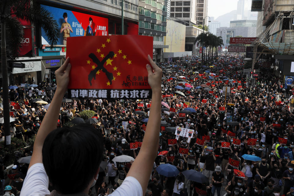 """A protester holds up a placard reading """"Aligning the regime, Anti Communist survival"""" as demonstrators march in Hong Kong, Sunday, Oct. 20, 2019. Hong Kong protesters again flooded streets on Sunday, ignoring a police ban on the rally and demanding the government meet their demands for accountability and political rights. (AP Photo/Kin Cheung)"""