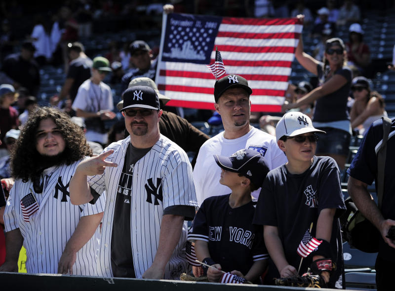 Yankee fans looks on as a United States flag commemorates the victims of the 9/11 attacks prior to the New York Yankees baseball game against the Los Angeles Angels, Sunday, Sept. 11, 2011, in Anaheim, Calif.  (AP Photo/Mark J. Terrill)