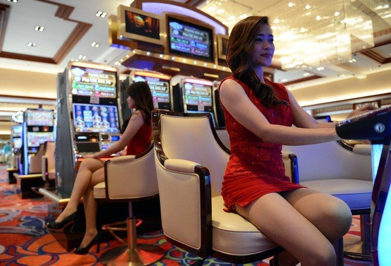 Employees of Solaire Manila Resorts and casino pose for a photo next to gaming machines inside the casino, in Manila, on March 14, 2013, ahead of its Saturday opening. Solaire Manila Resorts is the first of four huge entertainment venues slated to rise on reclaimed land on Manila Bay that industry and government officials hope will draw millions of newly well-off Asian visitors