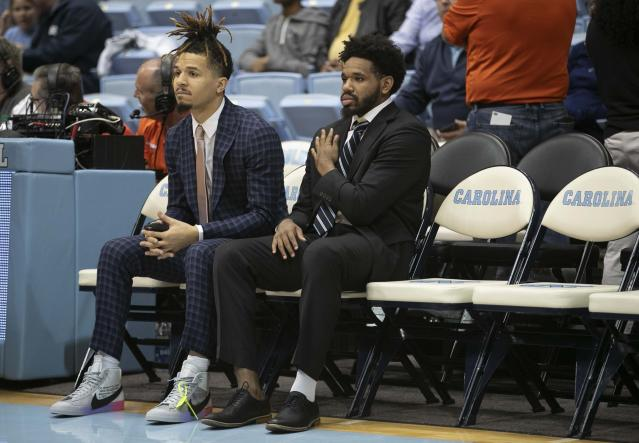 North Carolina's Cole Anthony, left,and Jeremiah Francis, both out with injuries, watch their teammates warm up for an NCAA college basketball game against Clemson on Saturday, Jan. 11, 2020, at the Smith Center in Chapel Hill, N.C. (Robert Willett/The News & Observer via AP)