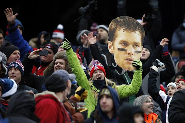 A fan holds a large photo of New England Patriots quarterback Tom Brady in the first quarter of an NFL football game against the Cleveland Browns, Sunday, Dec. 8, 2013, in Foxborough, Mass. (AP Photo/Elise Amendola)