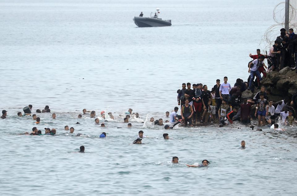 Moroccan citizens stand next to and swim around the fence between the Spanish-Moroccan border. (Reuters)