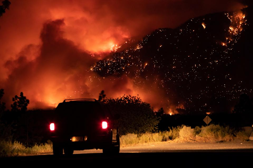 A motorist watches from a layby on the Trans-Canada Highway as a wildfire burns on the side of a mountain in Lytton (The Canadian Press via AP)