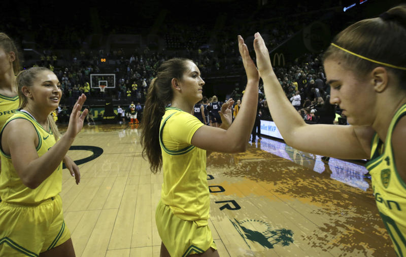 Oregon's Jaz Shelley, left, Taylor Chavez and Sabrina Ionescu, right congratulate each other after winning their NCAA college basketball game against Utah State 108-52 in Eugene, Ore., Wednesday, Nov. 13, 2019. (AP Photo/Chris Pietsch)