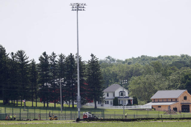 The Field of Dreams movie site, rear, is seen as construction of a baseball field continues, Friday, June 5, 2020, in Dyersville, Iowa. Major League Baseball is building the field a few hundred yards down a corn-lined path from the famous movie site in eastern Iowa but unlike the original, it's unclear whether teams will show up for a game this time as the league and its players struggle to agree on plans for a coronavirus-shortened season. (AP Photo/Charlie Neibergall)