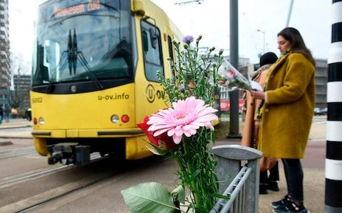 Flowers have been set up in tribute to victims at the site of the shooting in a tram - Credit: JOHN THYS/AFP