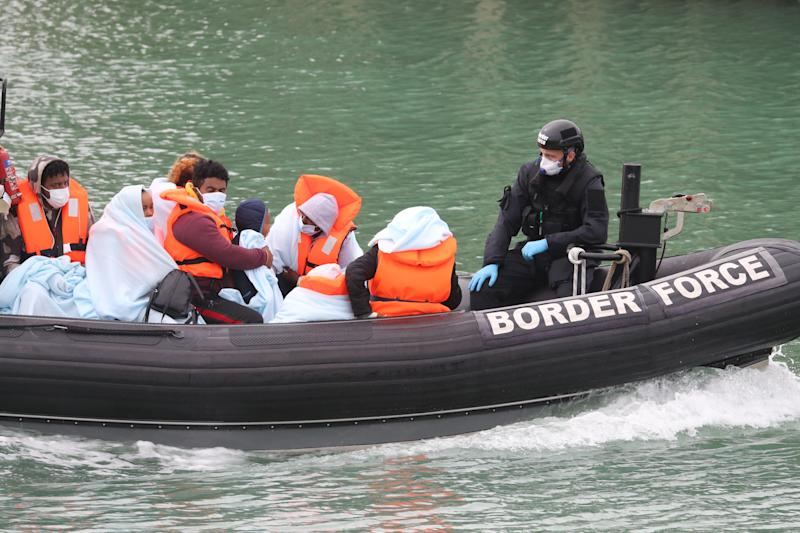 EDITORS NOTE: IMAGE PIXELATED BY PA PICTURE DESK A group of people thought to be migrants are brought into Dover, Kent, by Border Force officers following a small boat incident in the Channel.