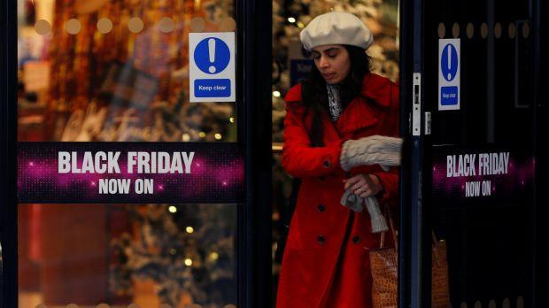 A woman in a coat and hat exits a store