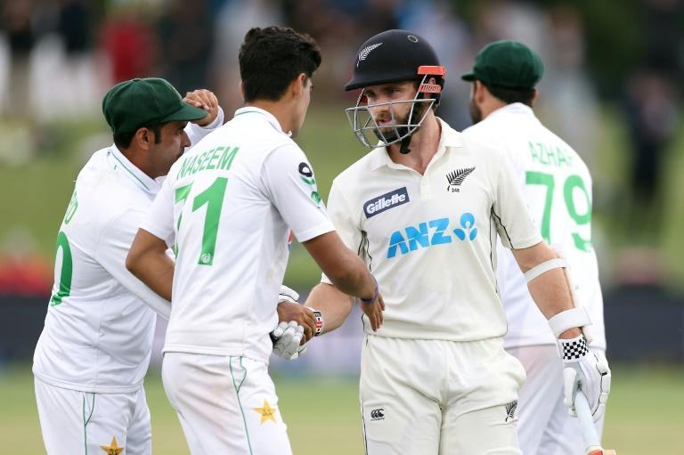 Pakistan's Abid Ali (left) and Naseem Shah congratulate Kane Williamson aftger he fell for 238
