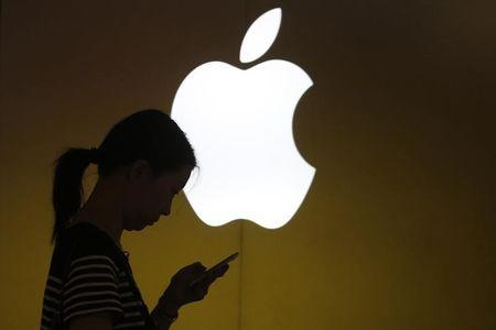 A woman looks at the screen of her mobile phone in front of an Apple logo outside an Apple store in downtown Shanghai