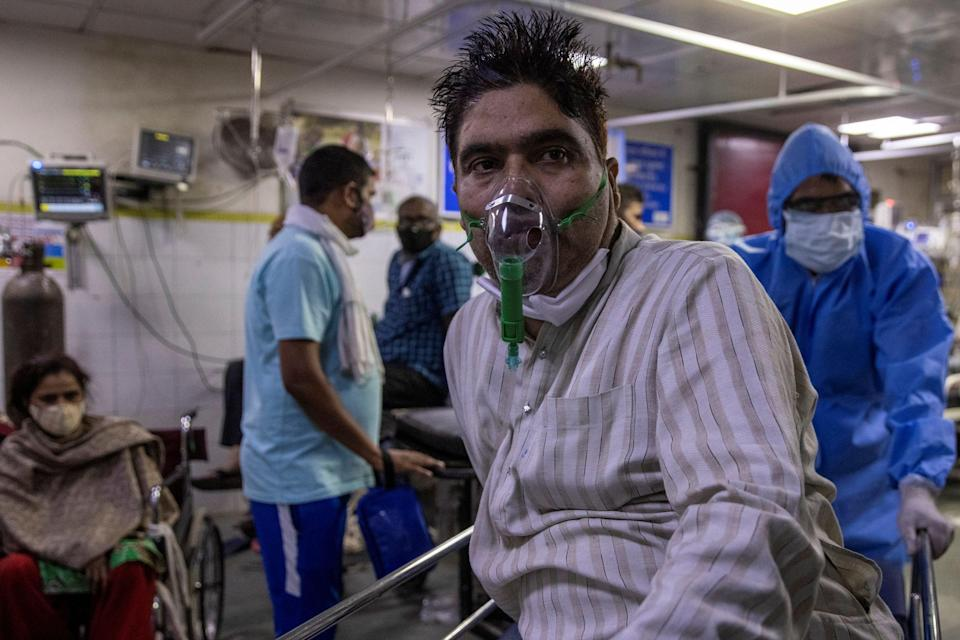 <p>A patient suffering from coronavirus is wheeled from the casualty ward in Lok Nayak Jai Prakas</p> (REUTERS)