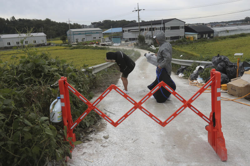 A quarantine official, right, sprays disinfectant solution to a man as a precaution against African swine fever near a pig farm in Paju, South Korea, Friday, Sept. 20, 2019. South Korea said Friday that it is investigating two more suspected cases of African swine fever from farms near its border with North Korea, as fears grow over the spread of the illness that has decimated pig herds across Asia. (AP Photo/Ahn Young-joon)
