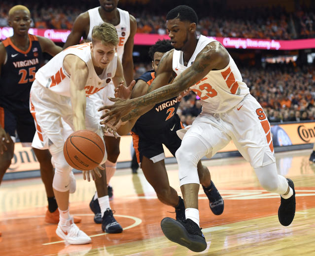 Syracuse forward Marek Dolezaj, left, and guard Frank Howard, right, reach for the ball against Virginia guard Braxton Key (2) during the first half of an NCAA college basketball game in Syracuse, N.Y., Monday, March 4, 2019. (AP Photo/Adrian Kraus)