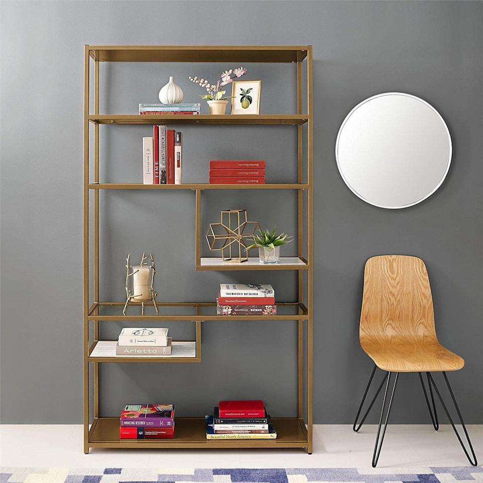 <p>Fans of modern furniture will lose their minds over the <span>Dorel Living Moriah Geometric Bookcase Etagere</span> ($237). The warm brass finish adds a trendy color to a visually interesting shelf.</p>