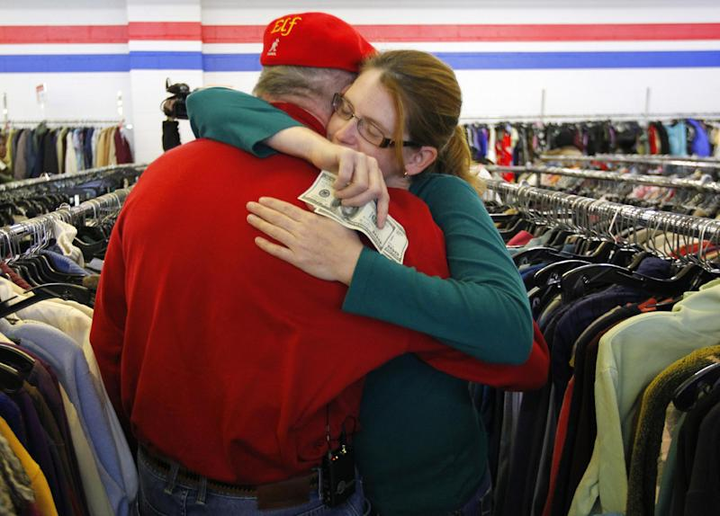 Janice Kennedy hugs Secret Santa after getting a $100 dollar bill from the wealthy philanthropist from Kansas City, Mo. while looking for clothes at the Salvation Army store in the boro of Staten Island, New York, N.Y., Thursday, Nov. 29, 2012. Secret Santa distributed $100 dollar bills to needy people at several locations in Elizabeth, N.J. and Staten Island. (AP Photo/Rich Schultz)