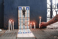 A soccer fan lights candles at the entrance of the home stadium of Gimnasia y Esgrima soccer team, coached by Diego Maradona, in La Plata, Argentina, Wednesday, Nov. 25, 2020. Maradona, the Argentine soccer great who was among the best players ever and who led his country to the 1986 World Cup title before later struggling with cocaine use and obesity, died from a heart attack on Wednesday at his home in Buenos Aires. He was 60. (AP Photo/Maria Paula Avila)