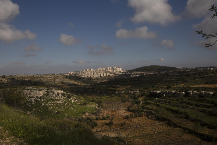 Sunlight peeks through clouds over a section of the West Bank Jewish settlement of Efrat, March 12, 2021. Israel went on an aggressive settlement spree during the Trump era, according to an AP investigation, pushing deeper into the occupied West Bank than ever before and putting the Biden administration into a bind as it seeks to revive Mideast peace efforts. (AP Photo/Maya Alleruzzo)