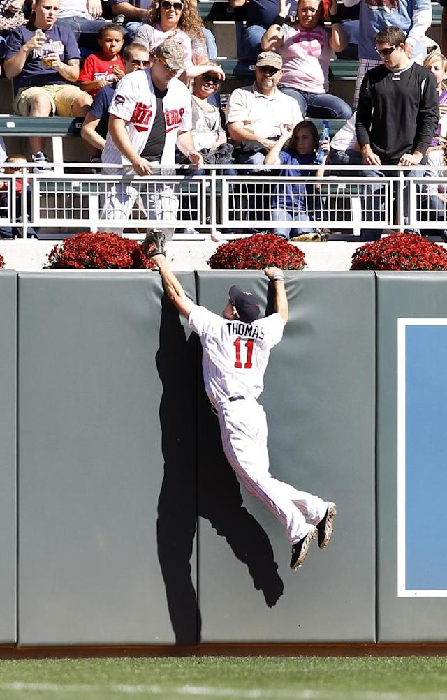 Minnesota Twins center fielder Clete Thomas (11) leaps but can't reach a two RBI home run by Cleveland Indians' Nick Swisher during the first inning of a baseball game in Minneapolis, Sunday, Sept. 29, 2013. (AP Photo/Ann Heisenfelt)