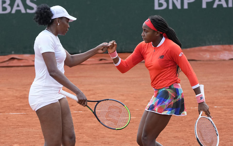 Venus Williams, left with doubles partner Coco Gauff of the United States bump fistsnafter winning a point against EllenPerez of Australia and Saisai Zheng of China in a first round women's doubles match day four of the French Open tennis tournament at Roland Garros in Paris, France, Wednesday, June 2, 2021. (AP Photo/Michel Euler)