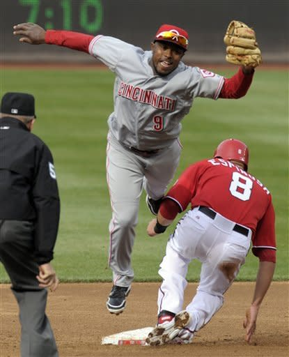 Cincinnati Reds second baseman Willie Harris (9) is unable to tag Washington Nationals' Danny Espinosa (8) during the third inning of their baseball game in Washington, Saturday, April 14, 2012. (AP Photo/Susan Walsh)