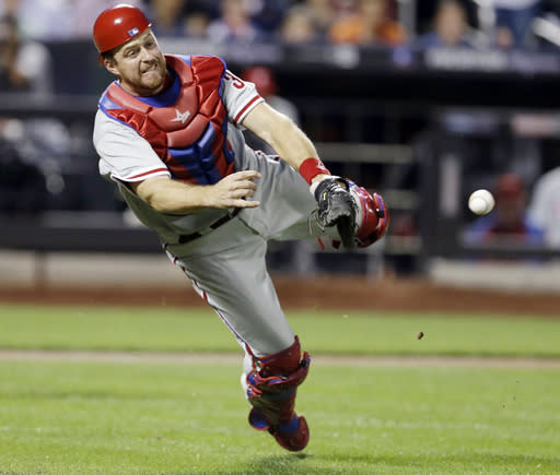 Philadelphia Phillies catcher Erik Kratz throws out New York Mets' Eric Young Jr. at first base during the third inning of a baseball game Tuesday, Aug. 27, 2013, in New York. (AP Photo/Frank Franklin II)