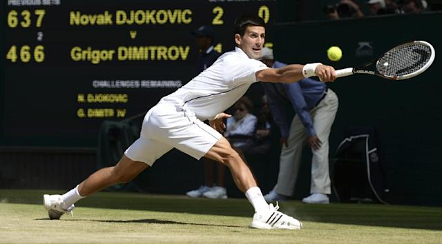 Novak Djokovic of Serbia stretches to reach a return to Grigor Dimitrov of Bulgaria during their men's singles semifinal match at the All England Lawn Tennis Championships at Wimbledon, London, Friday, July, 4, 2014. (AP Photo/Anthony Devlin, Pool)