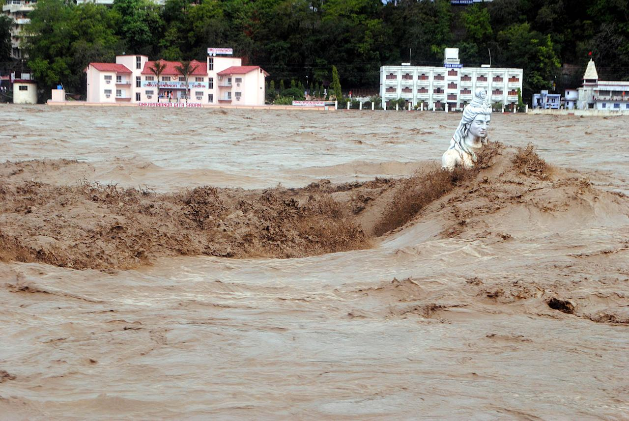 Fast moving water flows over a Hindu statue during a heavy monsoon rain in Rishikesh town in the Indian state of Uttrakhand on June 17, 2013. Heavy rains lashed parts of north India Monday, resulting in the deaths of at least 18 people, as the annual monsoon covered the country nearly two weeks ahead of schedule, officials said. More than a dozen people lost their lives due to record downpours in Uttarakhand state, situated in the foothills of the Himalayas, a local official said. AFP PHOTO/ STR