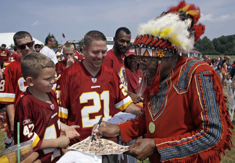 """FILE - In this Saturday, Aug. 4, 2012 file photo, Zena """"Chief Z"""" Williams signs autographs during fan appreciation day at the Washington Redskins' NFL football training camp at Redskins Park in Ashburn, Va. President Barack Obama says that if he owned the Washington Redskins, he would """"think about changing"""" the team name, wading into the controversy over a football nickname that many people deem offensive to Native Americans. Obama, in an interview on Friday, Oct. 4, 2013, said team names like the Redskins offend """"a sizable group of people."""" He said that while fans get attached to the nicknames, nostalgia may not be a good enough reason to keep them in place. (AP Photo/Alex Brandon)"""