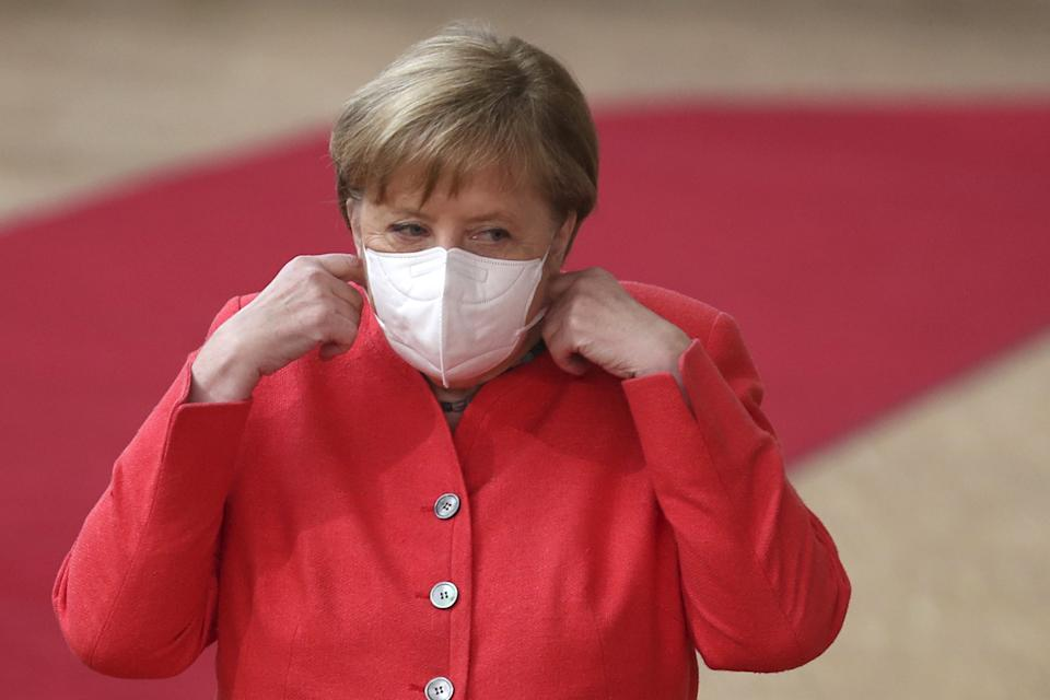 German Chancellor Angela Merkel prepares to remove her protective face mask prior to deliver a speech  as she arrives for a European Union Council in Brussels on July 17, 2020, as the leaders of the European Union hold their first face-to-face summit over a post-virus economic rescue plan. - The EU has been plunged into a historic economic crunch by the coronavirus crisis, and EU officials have drawn up plans for a huge stimulus package to lead their countries out of lockdown. (Photo by Francisco Seco / POOL / AFP) (Photo by FRANCISCO SECO/POOL/AFP via Getty Images)