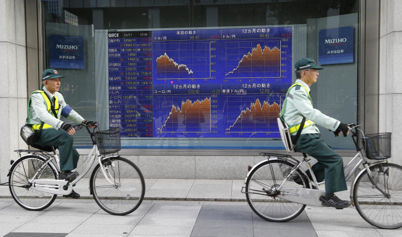 Illegal parking agents cycle past an electronic stock board of a securities firm in Tokyo, Thursday, Oct. 17, 2013 as Japan's bench mark Nikkei 225 Index closed at 14,588.51 after gaining 119.37 points, or 0.83 percent. An eleventh hour agreement that averted a U.S. government debt default boosted Asian stock markets Thursday. (AP Photo/Koji Sasahara)