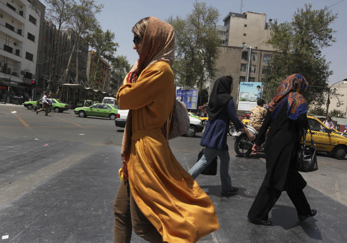 Iranian women cross a street a day after the presidential election in Tehran, Iran, Saturday, June 15, 2013. Iran's reformist-backed presidential candidate surged to a wide lead in early vote counting Saturday, a top official said, suggesting a flurry of late support could have swayed a race that once appeared solidly in the hands of Tehran's ruling clerics. The strong margin for former nuclear negotiator Rowhani may be enough to give him an outright victory and avoid a two-person runoff next Friday. (AP Photo/Vahid Salemi)
