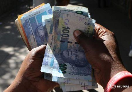 A street money changer counts South African Rands in Harare