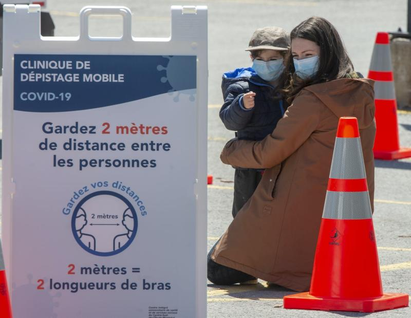 A masked woman hugs her masked child between orange pylons behind a sign for a mobile testing facility that instructs people to keep two metres apart.
