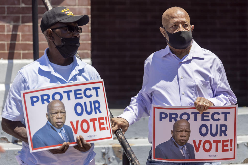 Henry Allen, left, and Charles Mauldin stand for the protection of voting rights at the John Lewis Advancement Act Day of Action, a voter education and engagement event taking place at Brown Chapel A.M.E. Church, Saturday, May 8, 2021, in Selma, Ala. Both men participated in the 1964 - 1965 Selma civil rights movement. (AP Photo/Vasha Hunt)