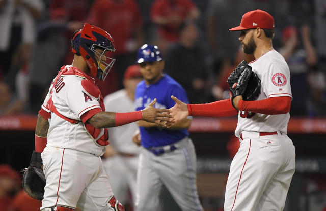 Los Angeles Angels catcher Martin Maldonado, left, and relief pitcher Justin Anderson congratulate each other after the Angels defeated the Toronto Blue Jays 8-5 in a baseball game Thursday, June 21, 2018, in Anaheim, Calif. (AP Photo/Mark J. Terrill)