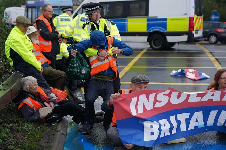 Police officers detain a protester from Insulate Britain occupying a roundabout leading from the M25 motorway to Heathrow Airport in London. Picture date: Monday September 27, 2021. (PA Wire)