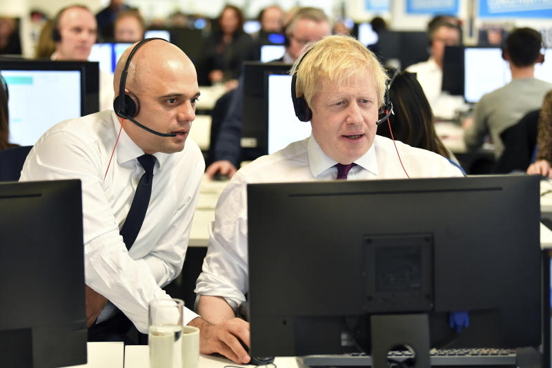 Britain's Prime Minister Boris Johnson, right and Chancellor of the Exchequer Sajid Javid speak to callers on the phone, at the Conservative Campaign Headquarters Call Centre, while on the General Election trail, in central London, Sunday, Dec. 8, 2019. Britain goes to the polls on Dec. 12. (Ben Stansall/Pool Photo via AP)