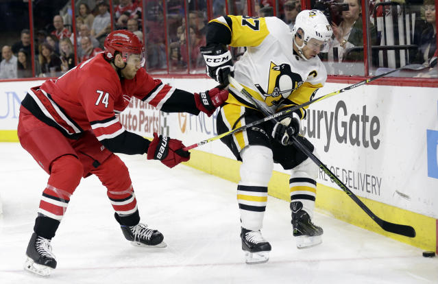 Carolina Hurricanes' Jaccob Slavin (74) and Pittsburgh Penguins' Sidney Crosby (87) chase the puck during the first period of an NHL hockey game in Raleigh, N.C., Friday, Feb. 23, 2018. (AP Photo/Gerry Broome)