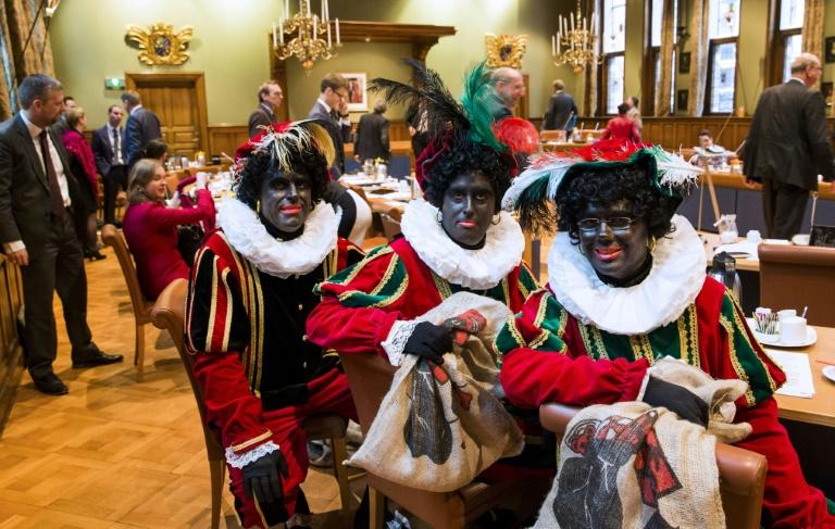 (From L) Dutch right wing PVV State members Ton van Kesteren, Matthijs Jansen and Dennis Ram dressed as Black Pete, the jolly sidekick of the Dutch Saint Nicholas, seen in Groningen, in November 2014