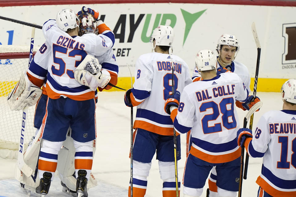 New York Islanders center Casey Cizikas (53) embraces goaltender Semyon Varlamov as teammates celebrate the team's win over the New Jersey Devils in an NHL hockey game Tuesday, March 2, 2021, in Newark, N.J. (AP Photo/Kathy Willens)
