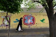 An Iranian woman walks next to a mural-covered wall on a street in the capital Tehran