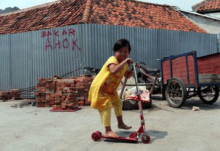 "A child rides a scooter in Luar Batang area in Jakarta, Indonesia April 18, 2017. The writing on the wall reads: ""Burn Ahok."" REUTERS/Beawiharta"