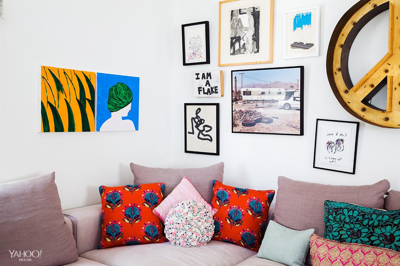 <p>There's a crooked painting here that makes me crazy, but I can deal with it. It's my living room. This peace sign is from Nickey Kehoe, funny enough. I love putting pillows in any room — especially mixing and matching. It adds personality and color. </p>