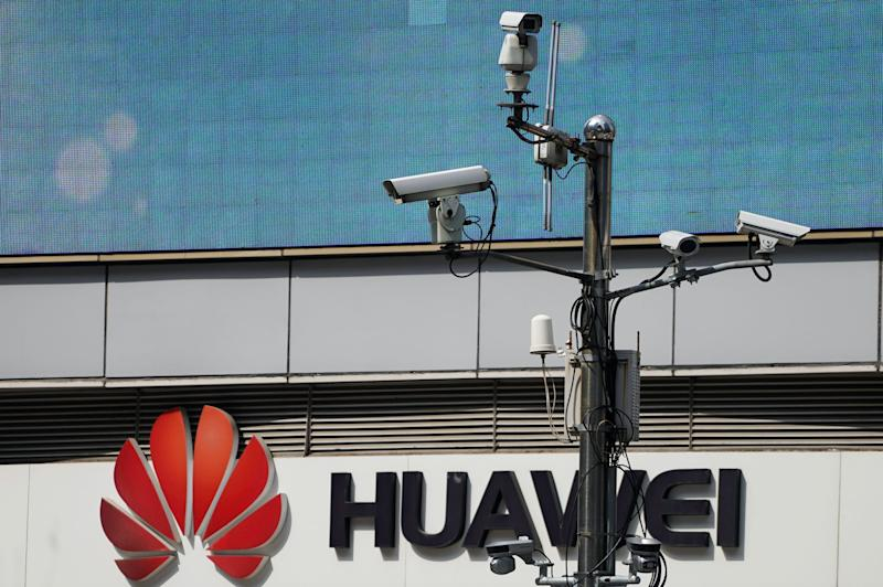 Surveillance cameras are seen next to a Huawei company logo outside a shopping mall in Shanghai, China March 7, 2019. REUTERS/Aly Song