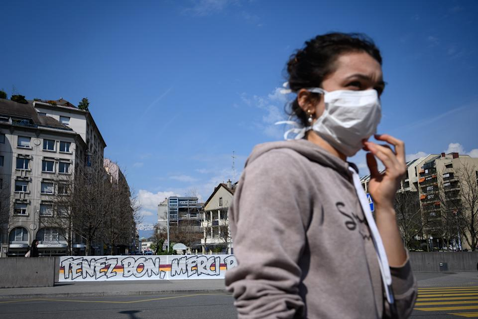 """A woman wearing a protective face mask walks by a giant banner reading : """"Hold on, thank you for everything"""" deployed in front of the Geneva University Hospitals (HUG) as a lockdown is in effect to prevent the spread of the COVID-19 caused by the novel coronavirus, in Geneva on March 20, 2020. (Photo by FABRICE COFFRINI / AFP) (Photo by FABRICE COFFRINI/AFP via Getty Images)"""