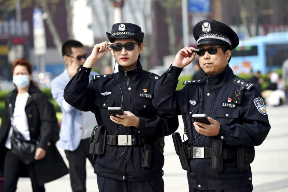 Police officers use A.I.-powered eyewear on the street in Luoyang, Henan province, China in April 2018.