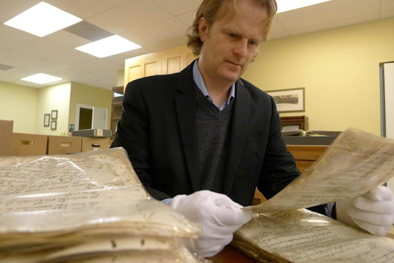 In this Saturday, Jan. 27, 2013 photo, University of South Florida professor J. Michael Francis looks at documents at the St. Augustine Catholic diocese in St. Augustine, Fla. The records date back to the year 1594, when Spanish colonialists settled in the area. Francis is working to digitize the records, which are fragile. The project is timely as Florida celebrates its 500th anniversary this year. Records show that by the time Jamestown was settled in Virginia in the early 1600's, St Augustine was a diverse home to 500 people of European descent, Native Americans, free and enslaved Africans. (AP Photo/Tamara Lush)