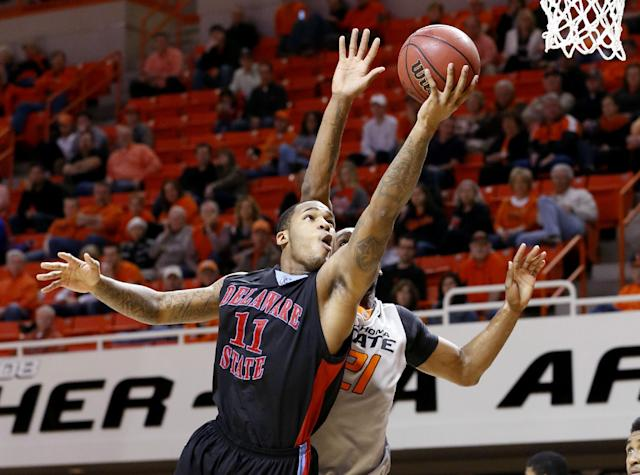 Delaware State guard DeAndre Haywood (11) shoots in front of Oklahoma State post Kamari Murphy (21) in the first half of an NCAA college basketball game in Stillwater, Okla., Tuesday, Dec. 17, 2013. Oklahoma State won 75-43. (AP Photo/Sue Ogrocki)
